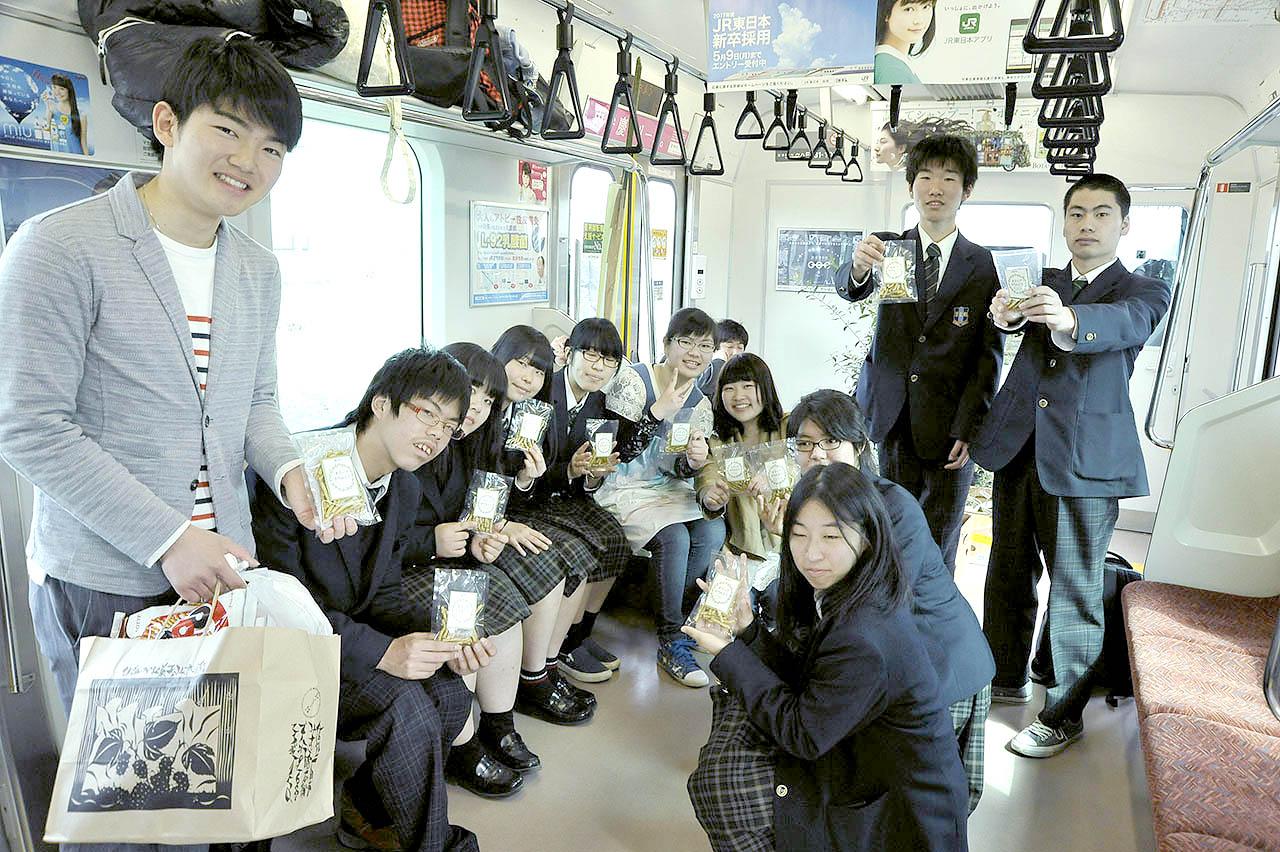 オリーブ列車に乗ったいわきの中高生たち。オリーブかりんとうを手に